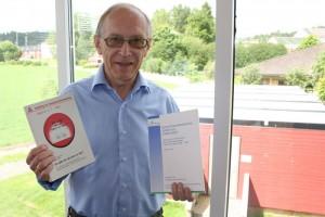 Jostein Holmen, førstefatter på publikasjonen og en av grunnleggerne for Helseundersøkelsen i Nord-Trøndelag og blodtrykksforskning i den, her med to av de første avhandlingene basert på HUNT-materiale
