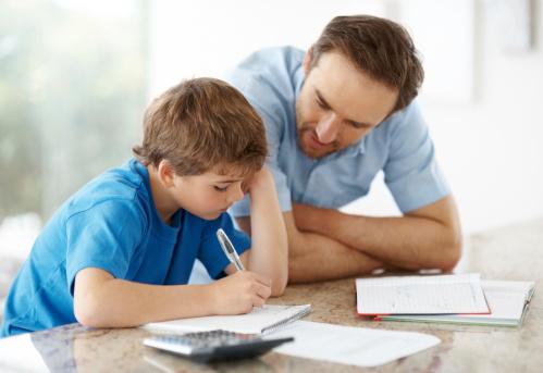 Ilustrasjon: Photos.com. Mann som hjelper sønnen med leksene