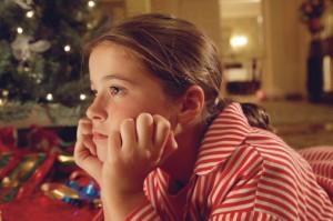 Illustrasjonsbilde: Tenkende jente med juletre i  bakgrunn