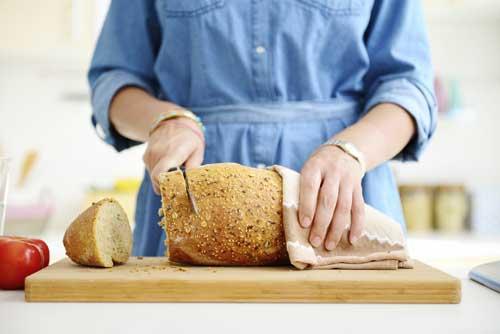 kvinne skjærer brød