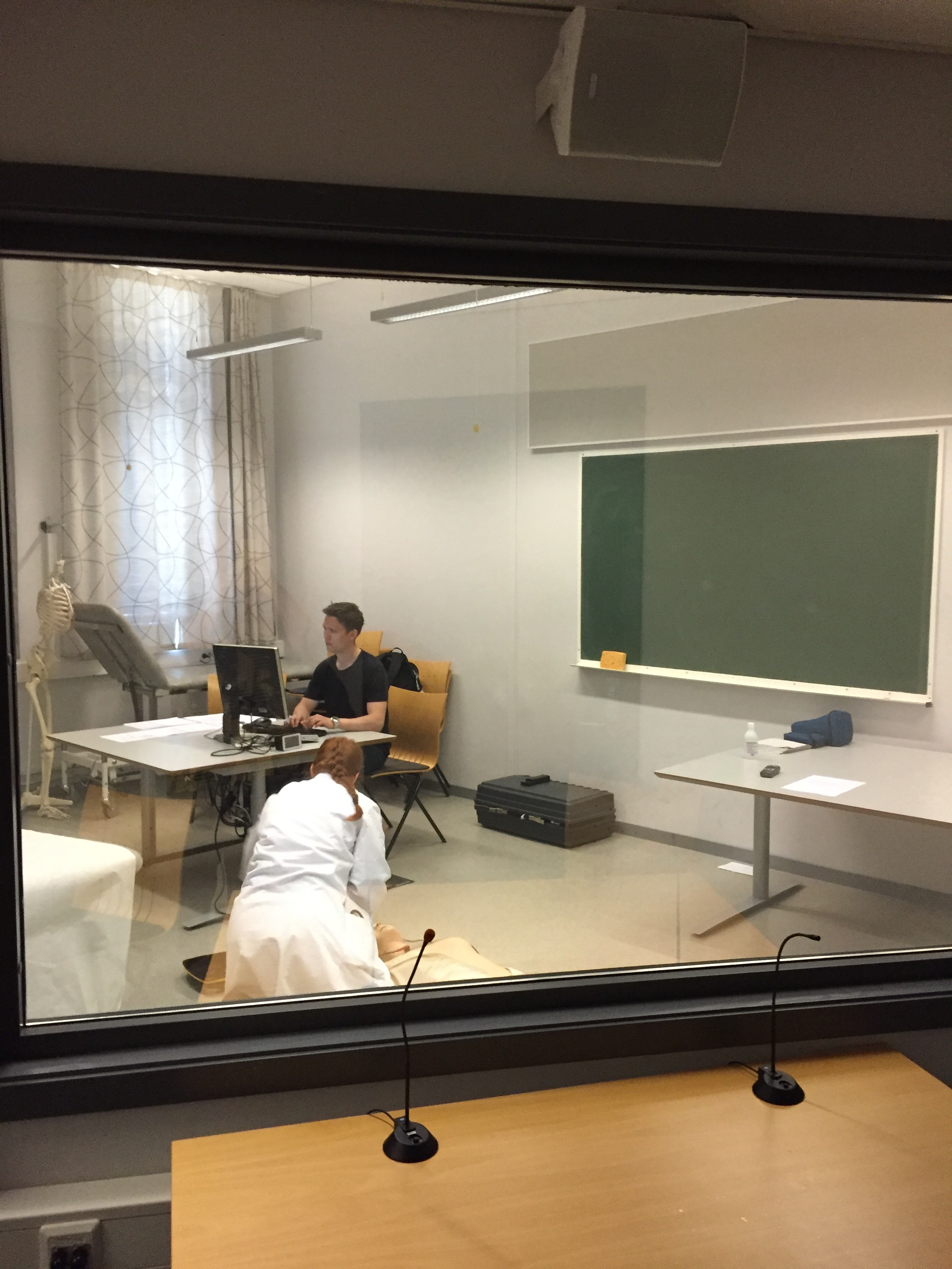 Eksaminator og anestesilege Helge Haugland, observerer student Oda Martine Reiertsen som gjennomfører hjerte-/lungeredning på dukke. Observert fra observasjonsrom på Øya helsehus. (Foto: Marie Thoresen)