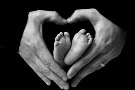 Hender og barneføtter i hjerteformasjon.
