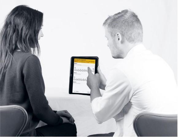 Fysioterapeut gjennomgår skjermdata med pasient