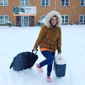 Illustrasjonsbilde av kvinne med rullekoffert i snø
