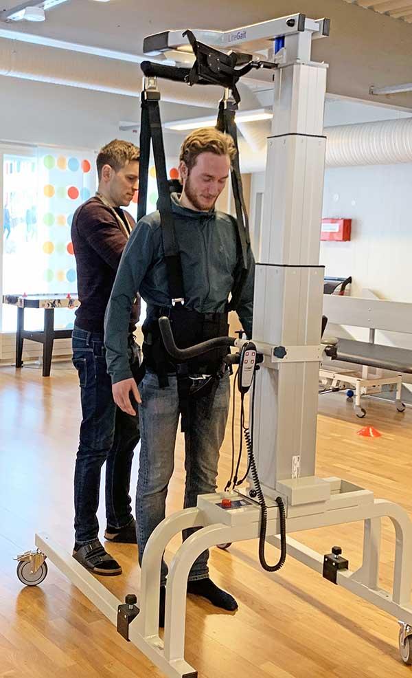 Teamleder viser et treningsapparat til student