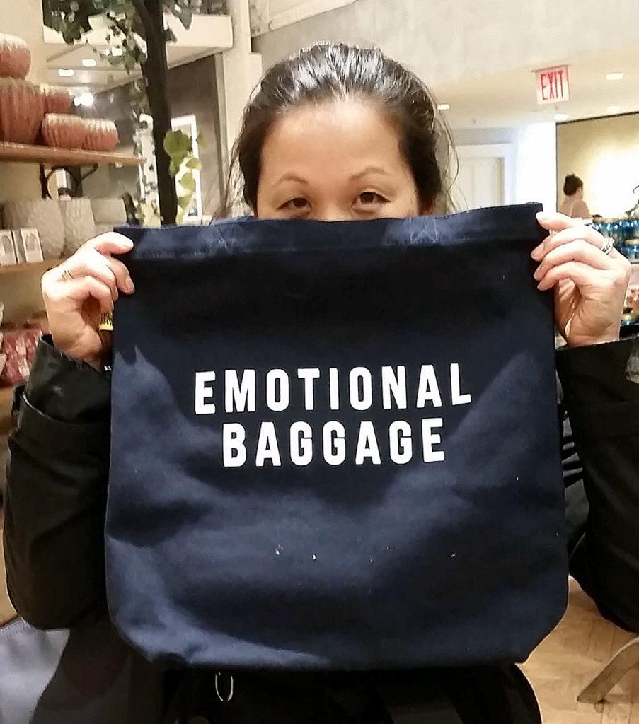 Foto av artikkelforfatteren som holder opp en pose med den engelskspråklige påskriften Emotional Baggage.