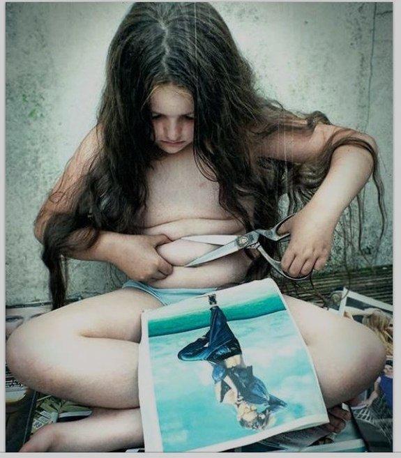 Kunstfoto tatt av Meg Gaiger, som viser et barn som prøver å klippe i magefettet med saks.
