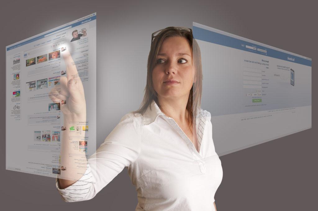 Kvinne som trykker på skjerm som viser facebook.