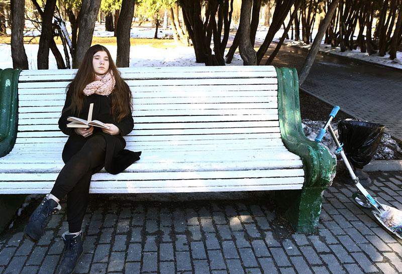 Kvinne som sitter på en benk.