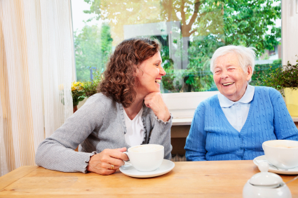Omsorgsperson drikker kaffe og snakker med eldre kvinne.