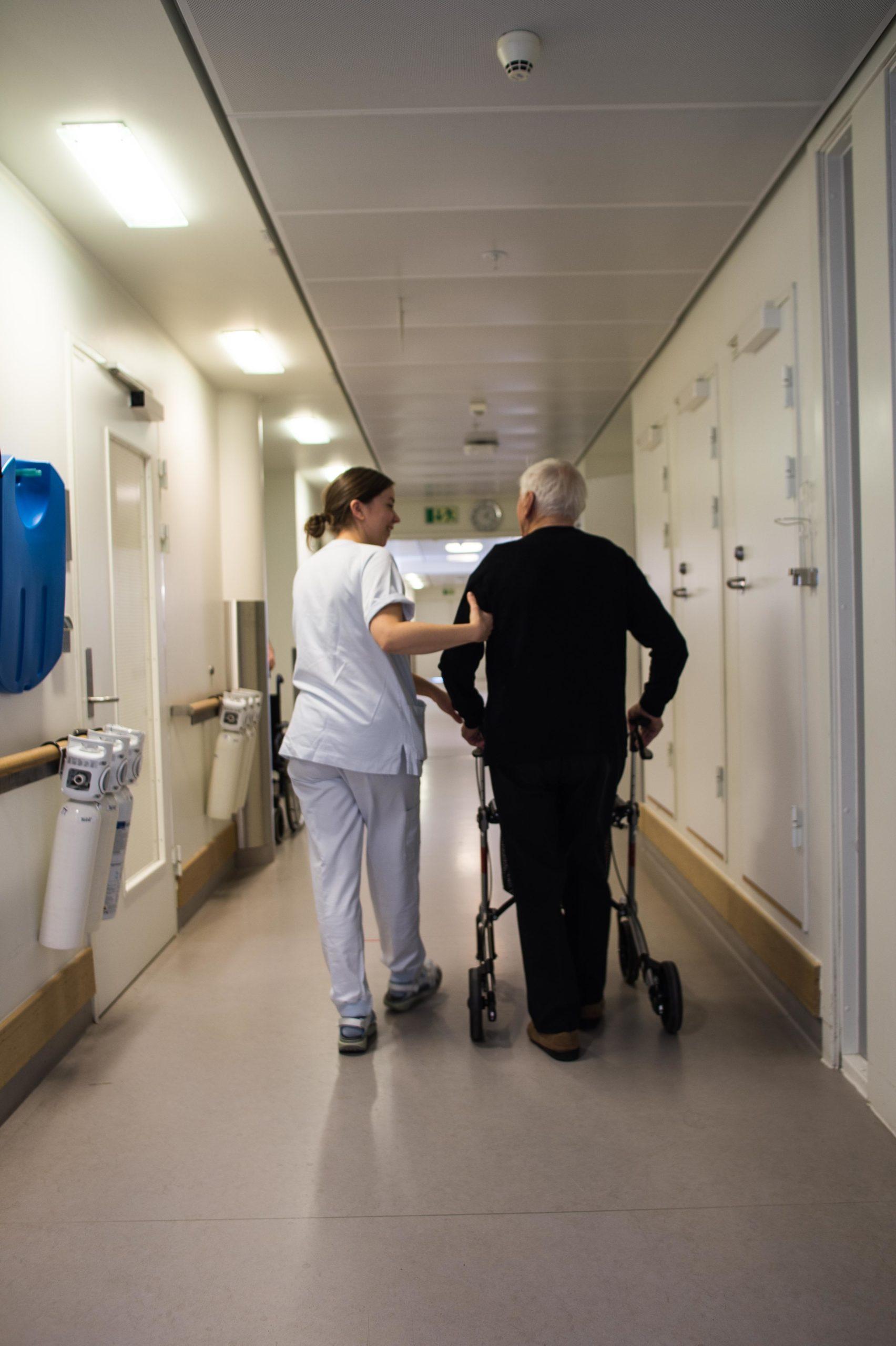 Sykepleier og eldre pasient med rullator går sammen i sykehuskorridor