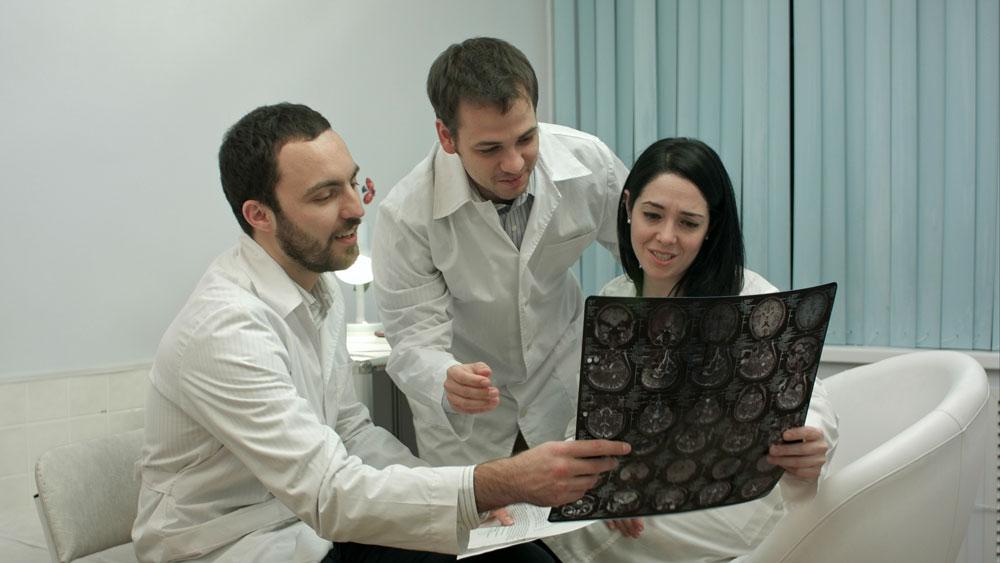Tre helsearbeidere undersøker røndgenbilde.